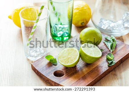 Fresh juicy limes, mint leaves and cocktail glasses on a wooden table. - stock photo