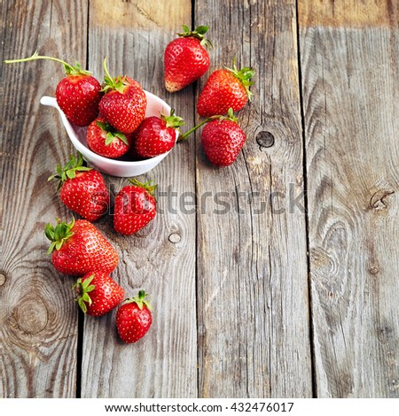 fresh juicy organic strawberries on an old wooden textured table top - stock photo