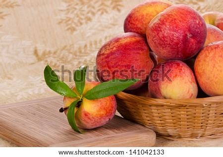 Fresh, juicy, peach fruits in a basket and cutting board - stock photo