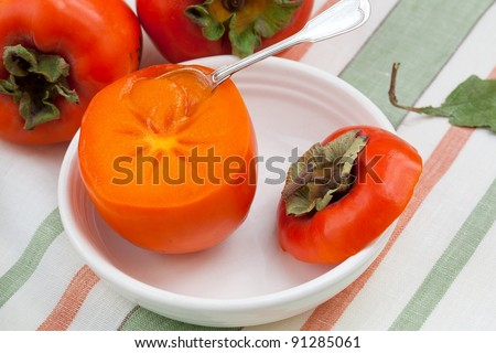 Fresh juicy persimmon in a white bowl with silver spoon on a striped linen napkin - stock photo
