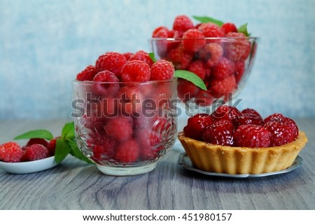 Fresh juicy raspberries in glass dish and tasty tart with raspberries. Selective focus - stock photo