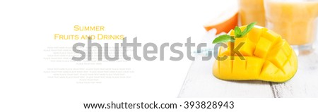 Fresh juicy summer cut mango, oranges and refreshment drinks on a wooden table on a white background, horizontal with place for text, copy space, closeup