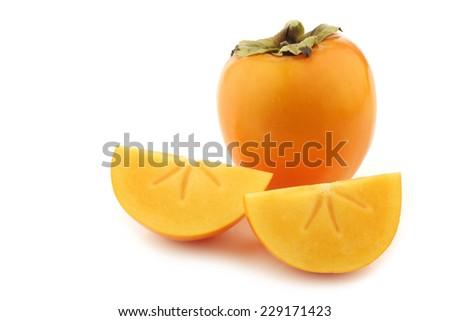 fresh kaki fruit and some cut pieces on a white background - stock photo
