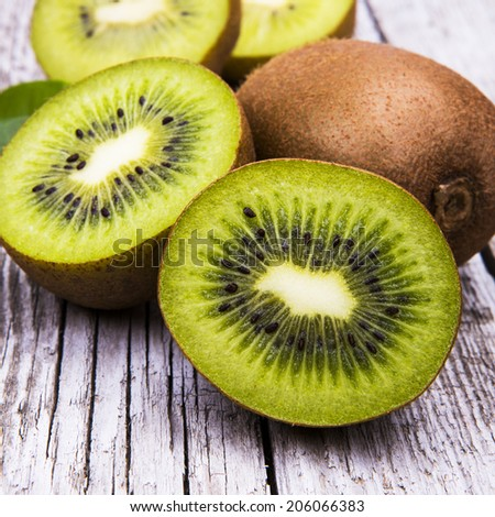 Fresh kiwi fruits on wooden table. Wood background. - stock photo