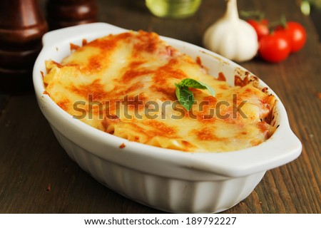 Fresh lasagna in a white container with basil - stock photo
