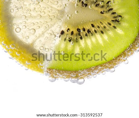 Fresh Lemon And Kiwi Slices In Carbonated Water Close Up - stock photo