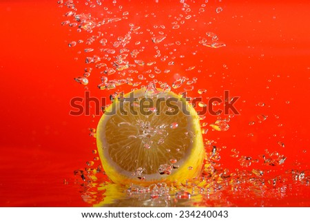 fresh lemon in water with bubbles. red background - stock photo