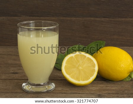 Fresh lemon juice in a glass placed on a wooden floor. - stock photo