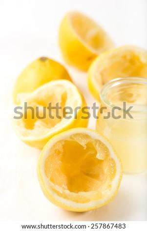 fresh lemon juice with squeezed lemons, isolated on white background, extreme close up, vertical - stock photo