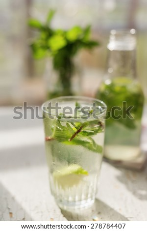 fresh lemonade with lemon, cane sugar, lime and mint in a glass - stock photo