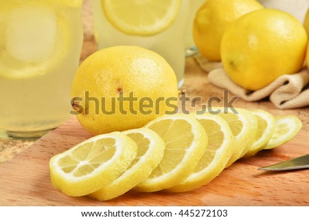 Fresh lemonade with lemon slices and whole lemons - stock photo