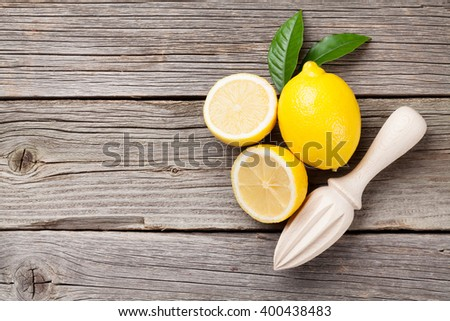 Fresh lemons and juicer on wooden table. Top view with copy space - stock photo