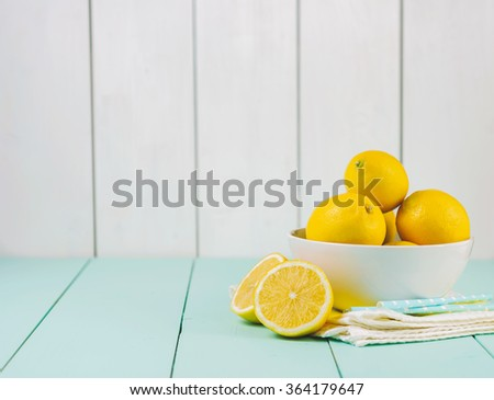 Fresh lemons in a white bowl on wooden background.Half of lemon. - stock photo