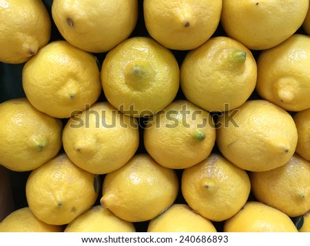 Fresh lemons stacked at a farmers market are fresh, ripe and ready to eat - stock photo