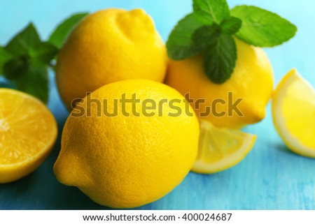 Fresh lemons with green leaves on blue table closeup - stock photo