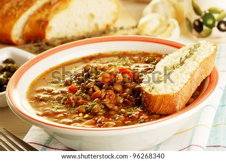 Fresh lentil stew in bowl with bread - stock photo