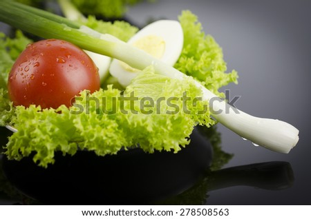 Fresh lettuce, boiled egg tomato, onions on a black table - stock photo