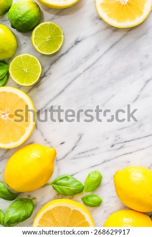 Fresh lime and lemon citrus fruits on marble background. Copy paste your own text. Empty space next to yellow and green juicy fresh fruits on white bakground. - stock photo