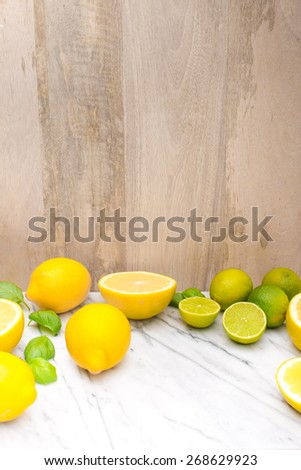 Fresh lime and lemon citrus fruits on marble table. Copy and paste your own text. Empty space next to yellow and green juicy fresh fruits on white bakground. - stock photo