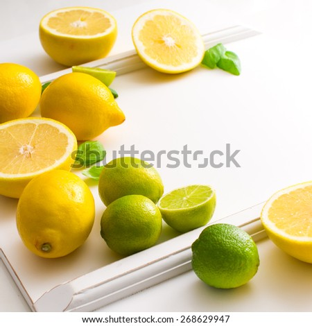 Fresh lime and lemon citrus fruits on white background. Copy paste your own text. Empty space next to yellow and green juicy fresh fruits on white bakground. - stock photo