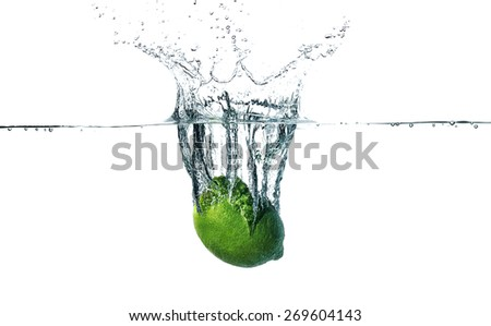 Fresh lime falling into water, isolated on white background - stock photo