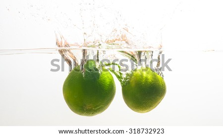 Fresh limes, drop in the water  - stock photo