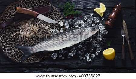 Fresh liza fish on ice on a black wooden table top view - stock photo