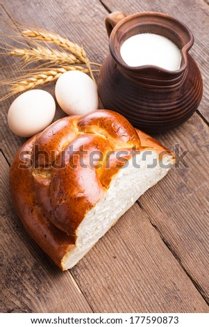 Fresh loaf of challah with milk and eggs on the table - stock photo