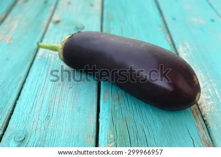Fresh long thick purple aubergine on blue table - stock photo