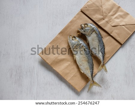 Fresh mackerel or tuna steamed fish put on paper bag - stock photo