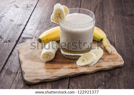 Fresh made Banana Milkshake on wooden background - stock photo