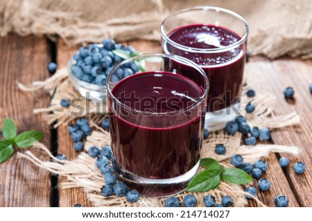 Fresh made Blueberry Juice with some fruits on wooden background - stock photo