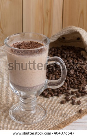 Fresh Made Chocolate Banana Smoothie on a wooden table with coffee and spices. Selective focus. Milkshake. Protein diet. Healthy food concept. Drink, coffee beans. - stock photo