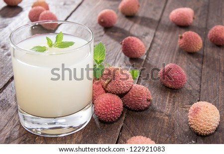 Fresh made Lychee Juice on wooden background - stock photo