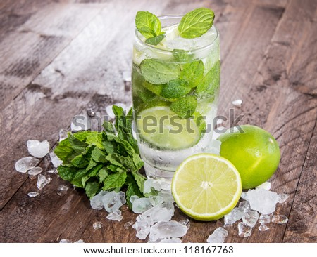 Fresh made Mojito with ingredients on wooden background - stock photo