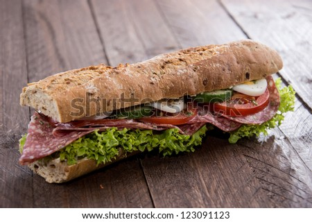 Fresh made Salami Sandwich on wooden background - stock photo