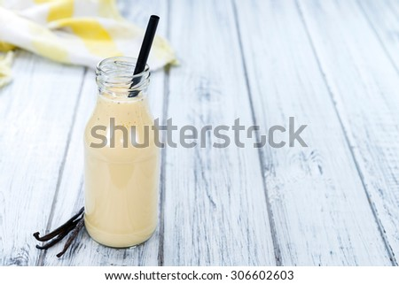 Fresh made Vanilla Milk (close-up shot) on wooden background - stock photo