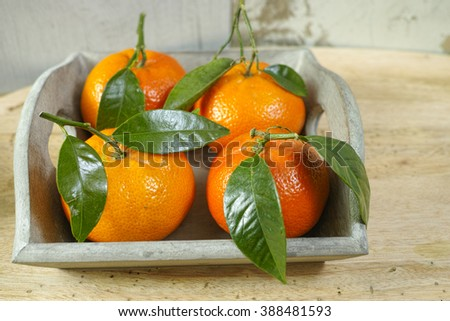 Fresh mandarin oranges fruit with green leaves on wooden background - stock photo