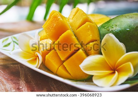 fresh mango in the plate on a wooden tabel with tropical background. Soft focus. - stock photo