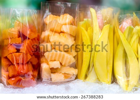 Fresh mango, melon and papaya fruits sliced in plastic bags in a street market. - stock photo