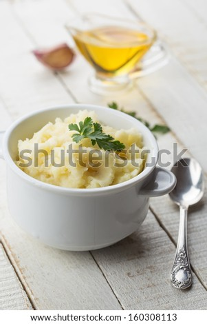 Fresh mashed potatoes in white bowl on wooden background. Selective focus. - stock photo