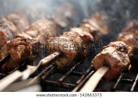 Fresh meat on a steel skewer in a smoke at brazier - stock photo