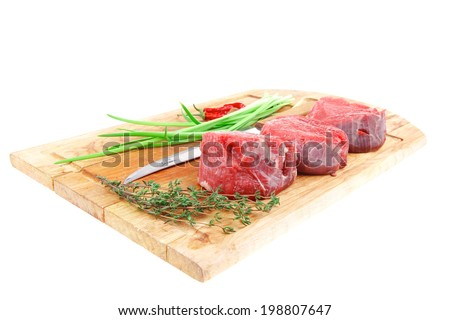 fresh meat : raw beef fillet on wooden board with thyme and red hot dry pepper ready to prepare . isolated over white background - stock photo