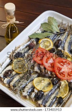 Fresh Mediterranean sardines, mackerel fishes, crispy baked with organic tomato, laurel, rosemary and tasty olives, selective focus - stock photo