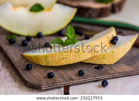 fresh melon and blueberries on a wooden cutting board. selective focus - stock photo