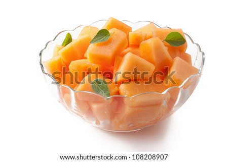 Fresh melon cubes with mint leaves in glass bowl - stock photo