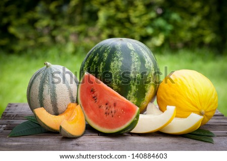 Fresh melons on wooden ground - stock photo