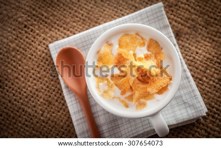 Fresh milk and cereal flakes in bowl on wooden background for breakfast. - stock photo