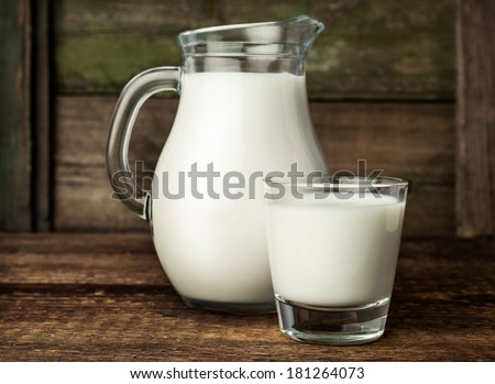 fresh milk in glass jug and glass on wooden background - stock photo