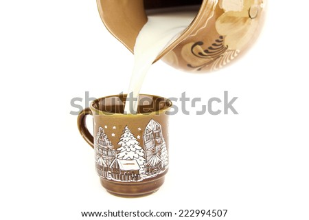fresh milk is poured out of an old clay jug - stock photo